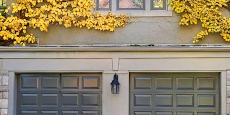 The door Master- Black double garage door with yellow leaves